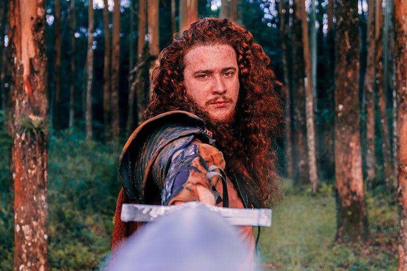 Ein Ritter, der ein Schwert im Wald hält