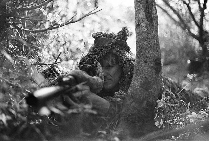 Ein Soldat mit einem Scharfschützen, der im Wald auf dem Boden liegt