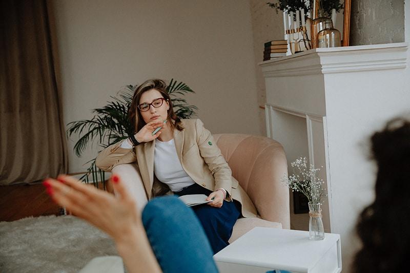 Ein Therapeut hört einem Klienten zu, während er im Sessel sitzt