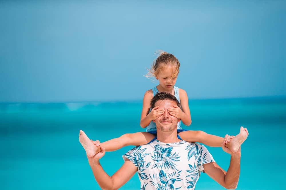 Ein Vater am Meer trägt seine Tochter auf den Schultern