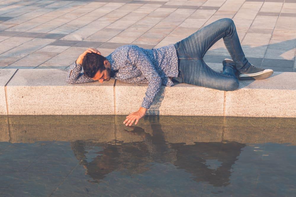 Ein gutaussehender Mann liegt an einem Betonufer und schaut auf das Wasser