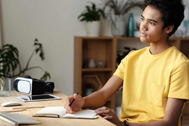 Ein junger Mann lernt, während er am Schreibtisch sitzt