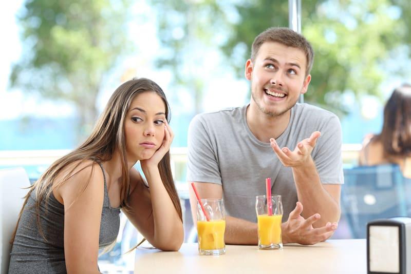Ein lächelnder Mann spricht mit einer Frau, die gelangweilt aussieht, während sie zusammen im Café sitzt