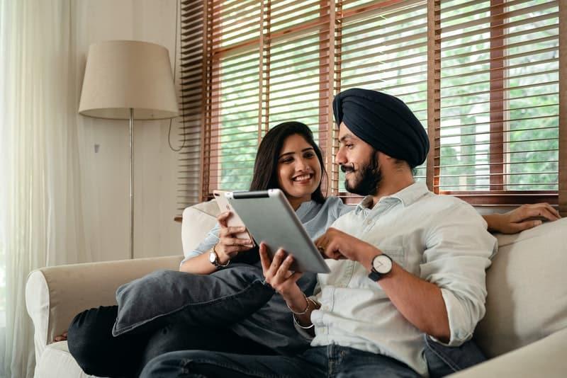 Ein lächelndes Paar mit Tabletten in den Händen sitzt auf der Couch und redet