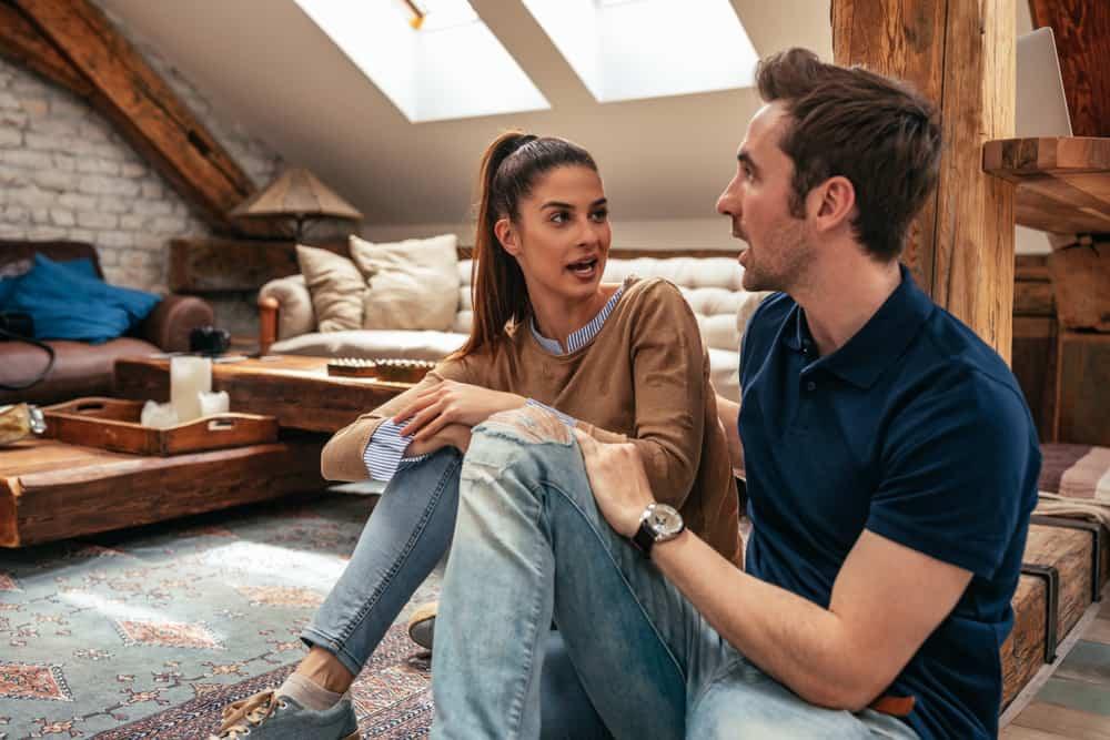 Ein liebevolles Paar sitzt auf dem Boden im Haus und redet