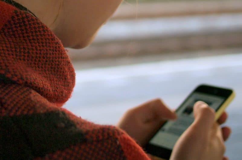 Eine Frau geht die Straße entlang und schreibt am Telefon