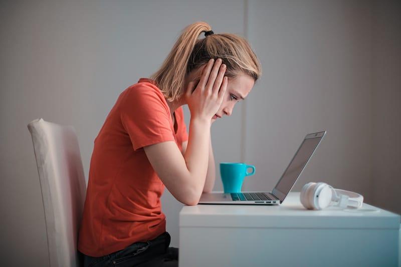 Eine Frau in einem Problem sitzt vor dem Laptop und hält den Kopf