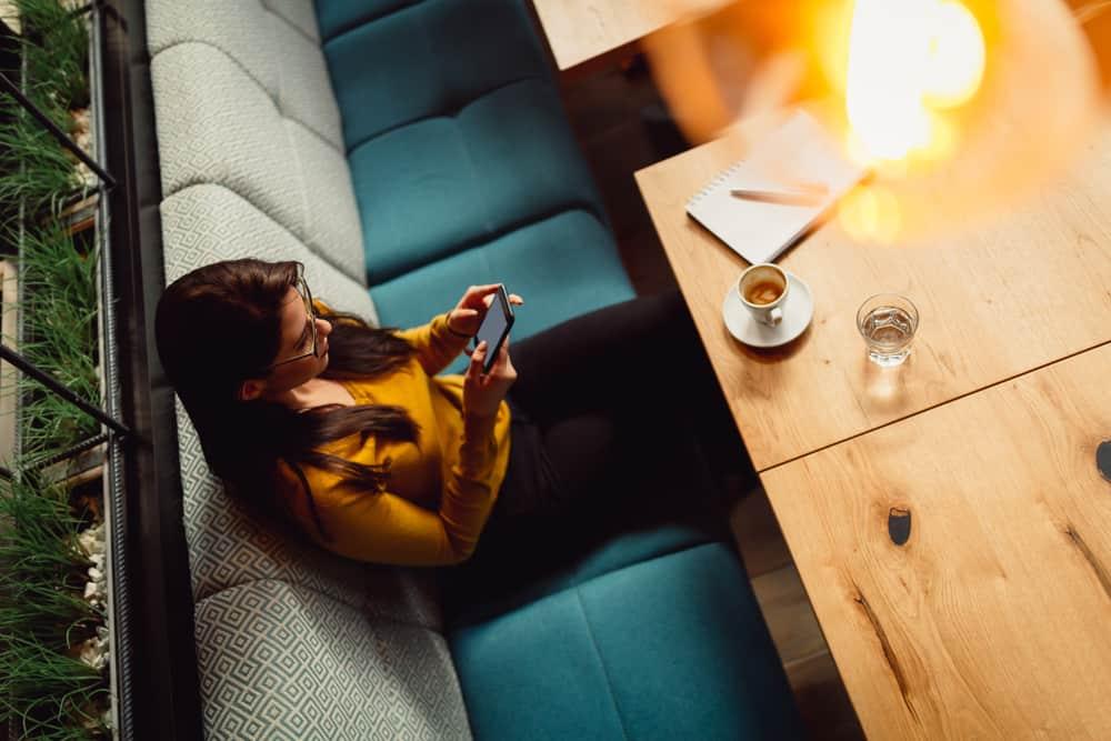 Eine Frau in einem gelben Pullover sitzt in einem Café und benutzt ein Smartphone