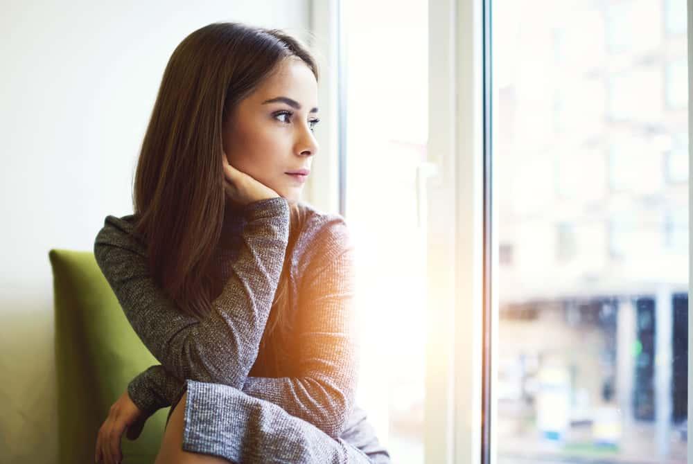 Eine Frau in einem grauen Kleid am Körper sitzt am Fenster und denkt nach