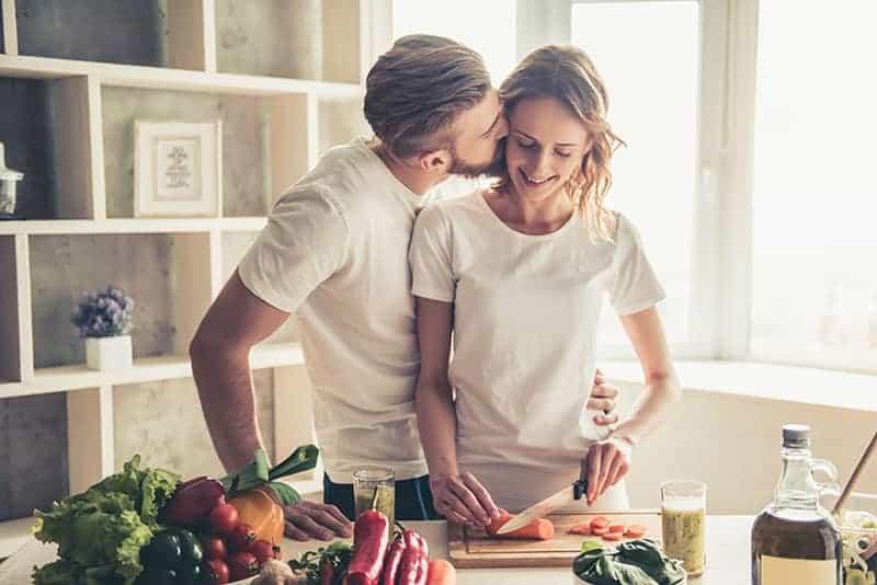 Eine Frau kocht das Mittagessen und ein Ehemann küsst sie auf die Wange
