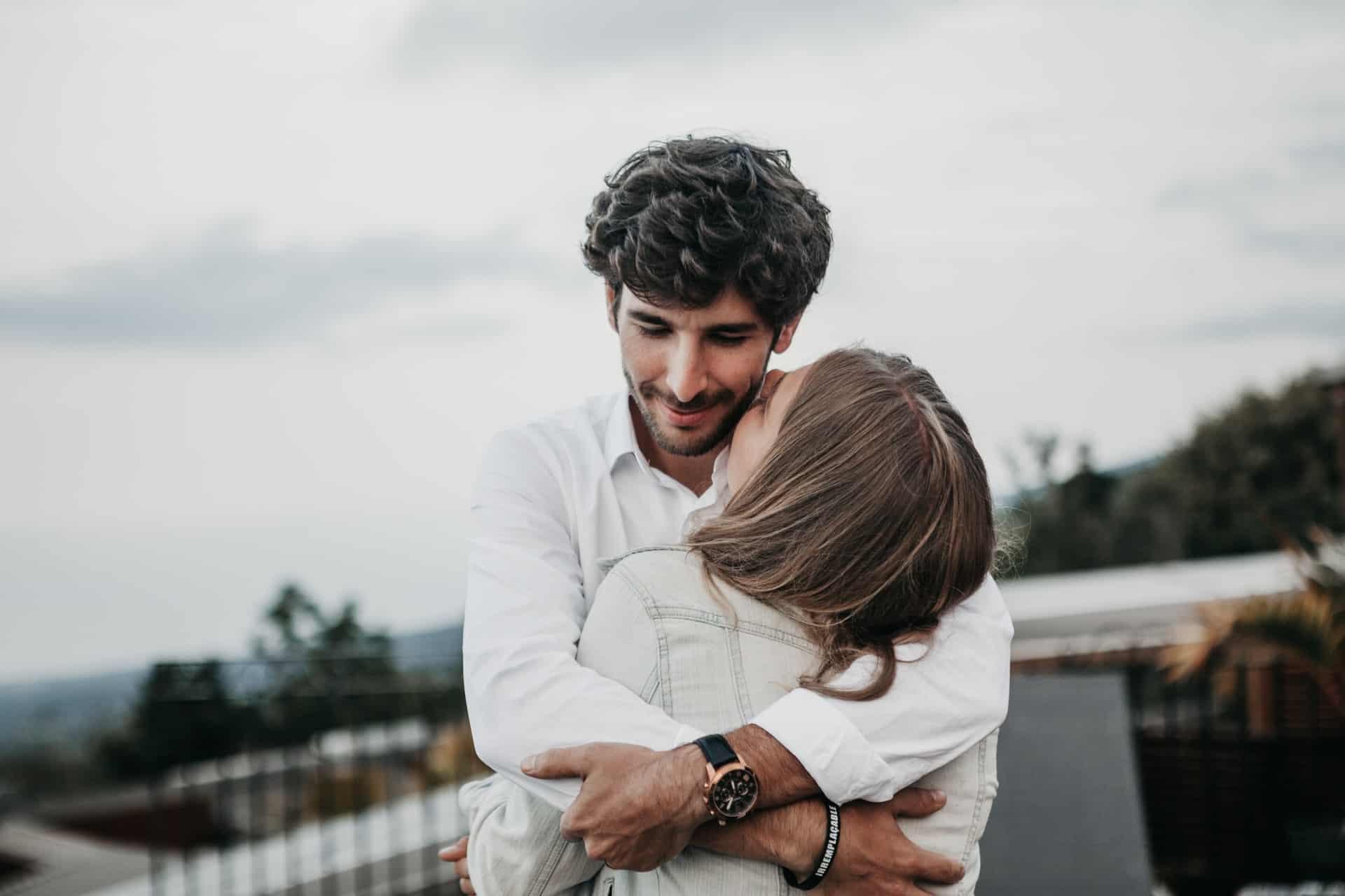 Eine Frau küsst einen Mann auf den Hals