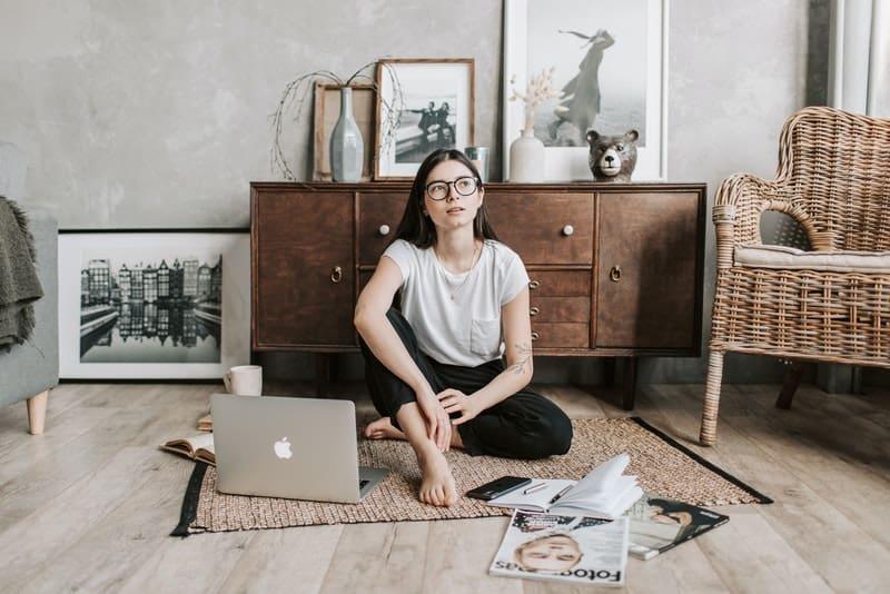 Eine Frau mit Brille sitzt auf dem Boden und denkt nach