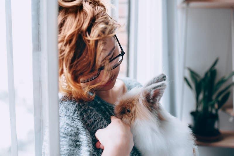 Eine Frau mit Brille sitzt auf dem Boden und hält ein Zwergkaninchen in den Armen