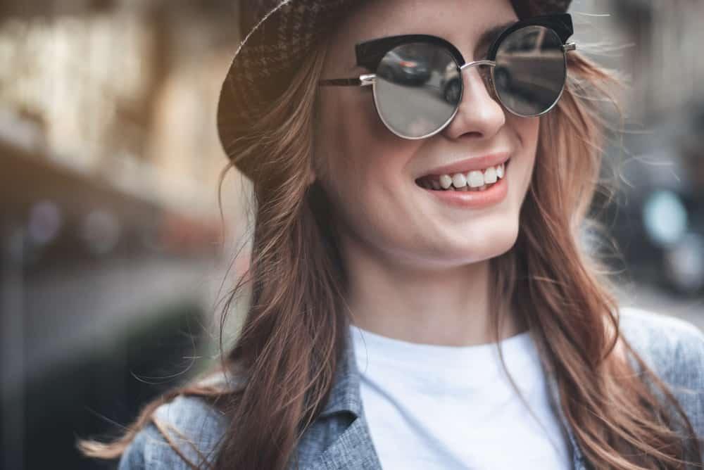 Eine Frau mit Brille und Hut lacht