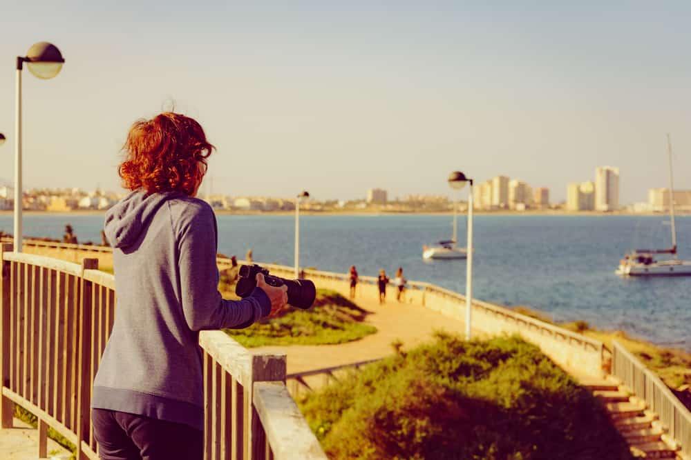 Eine Frau mit einer Kamera steht und beobachtet das Meer
