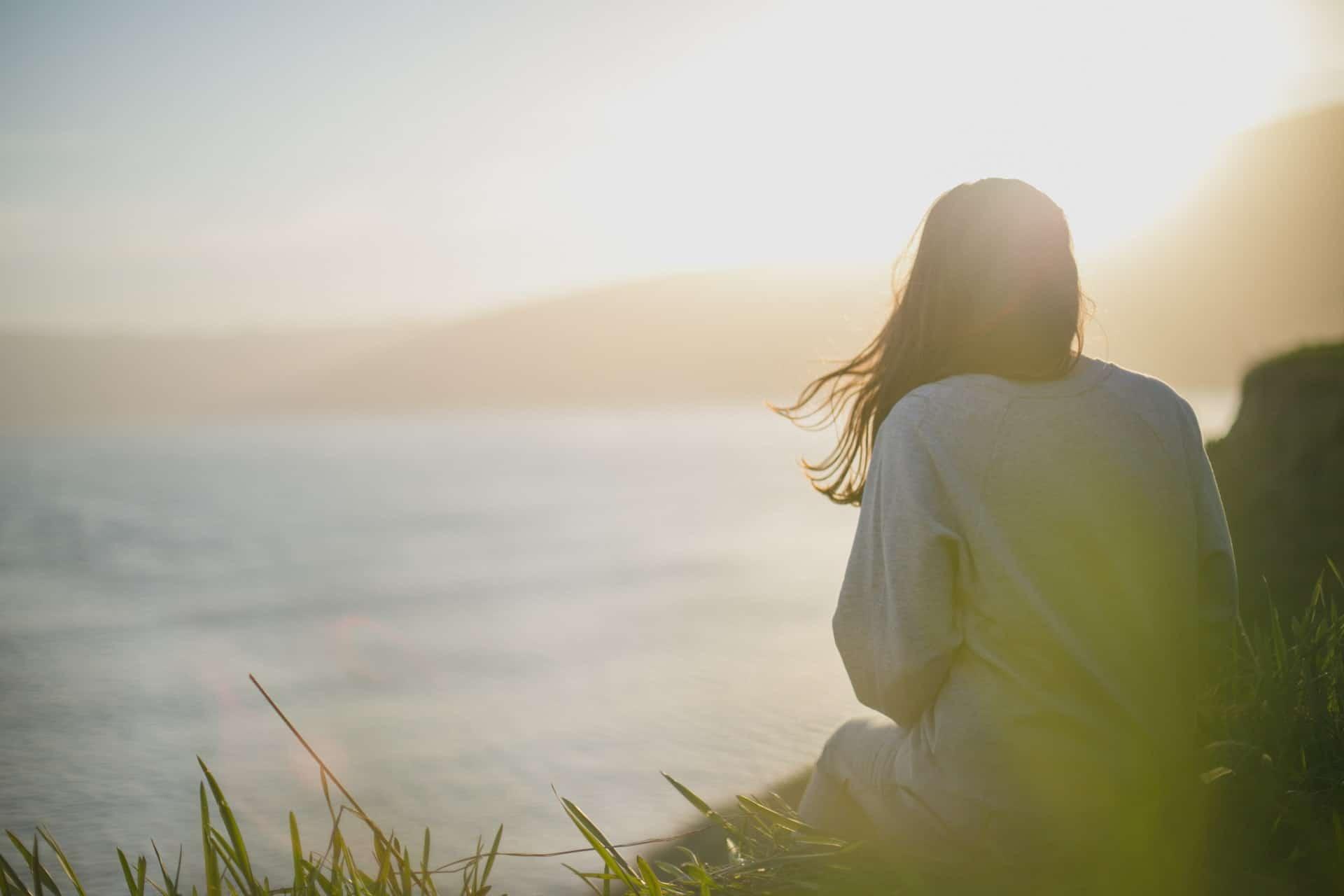 Eine Frau mit langen schwarzen Haaren sitzt mit dem Rücken zum Gras