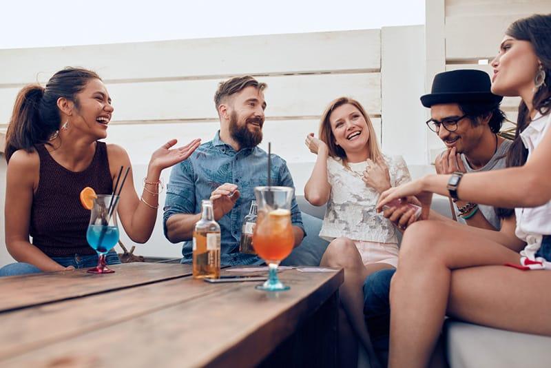 eine Gruppe lachender Freunde, die mit Getränken am Tisch sitzen