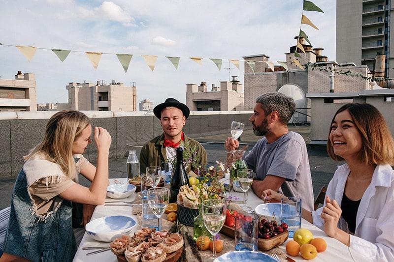 Eine Gruppe von Freunden sitzt am Tisch auf dem Dach und feiert etwas