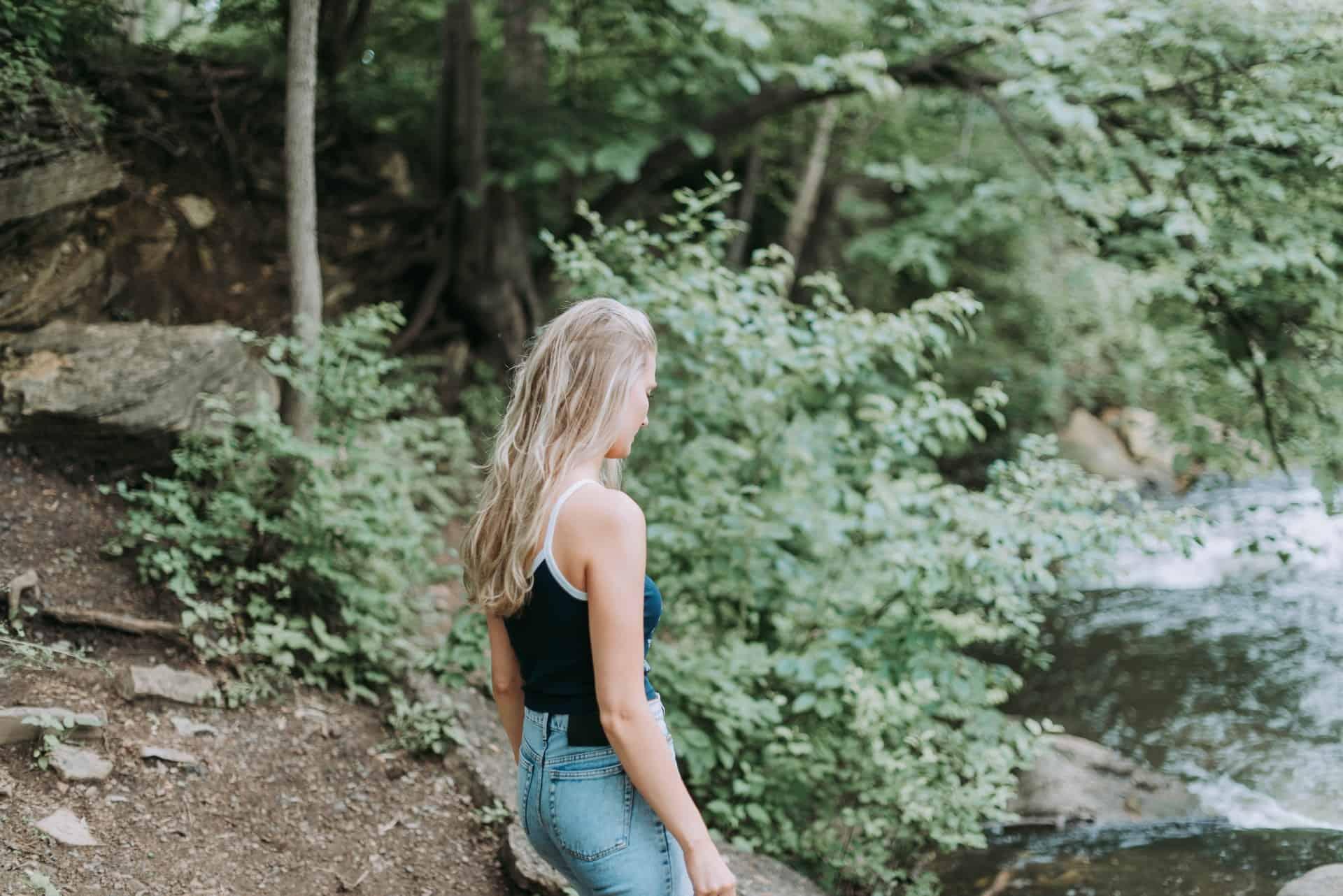 Eine blonde Frau sitzt am Fluss