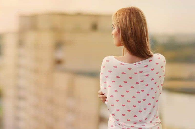 Eine blonde Frau steht mit dem Rücken zum Balkon