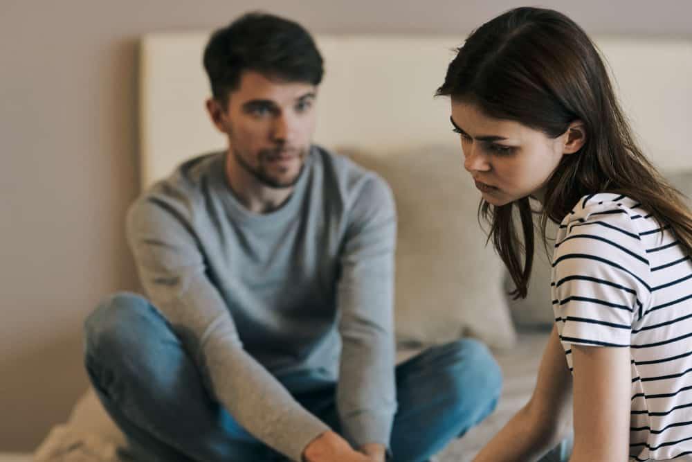 Eine depressive Frau sitzt neben einem Mann
