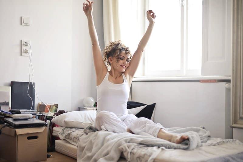 Eine lächelnde Blondine streckt sich am Morgen nach dem Aufwachen