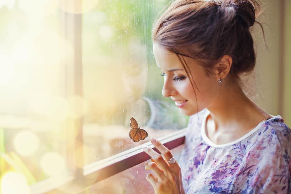 Eine lächelnde Frau am Fenster berührt einen Schmetterling