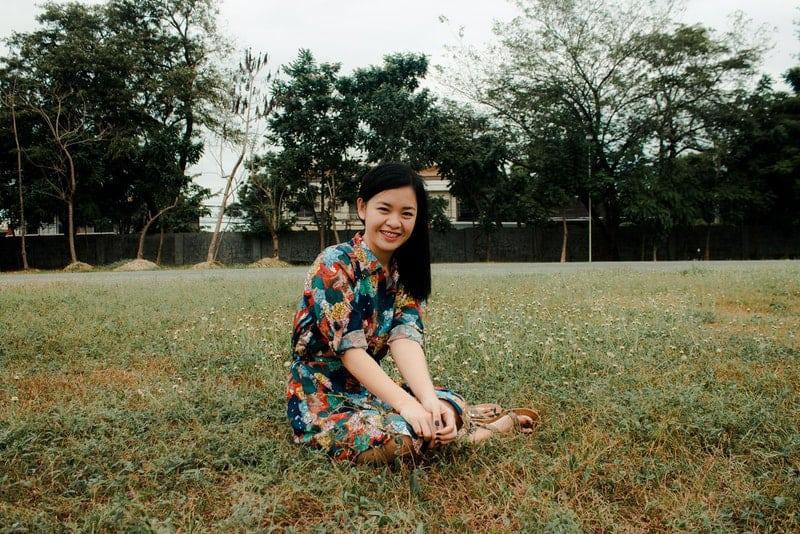 Eine lächelnde asiatische Frau sitzt im Gras