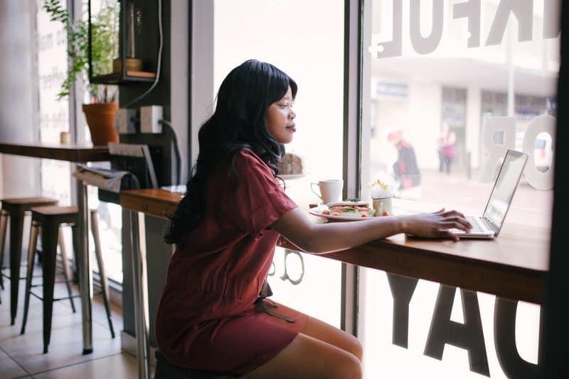 Eine schwarze Frau in einem Café benutzt einen Laptop