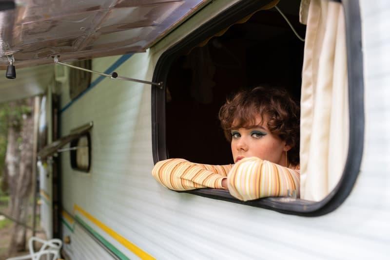 Eine traurige kurzhaarige Frau steht am Fenster des Wohnwagens gelehnt