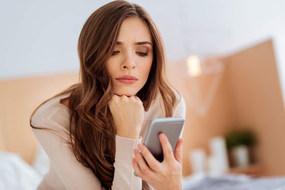 Eine wütende Frau schaut auf ihr Handy