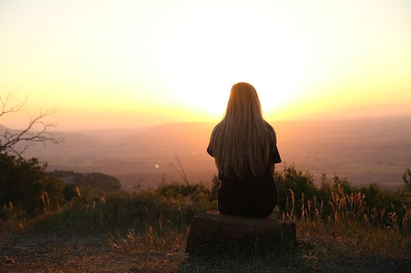 Frau, die den Sonnenuntergang allein beim Sitzen auf dem Felsen beobachtet