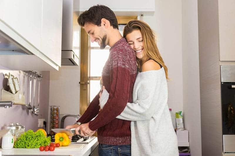 Frau, die einen Mann umarmt, der kocht