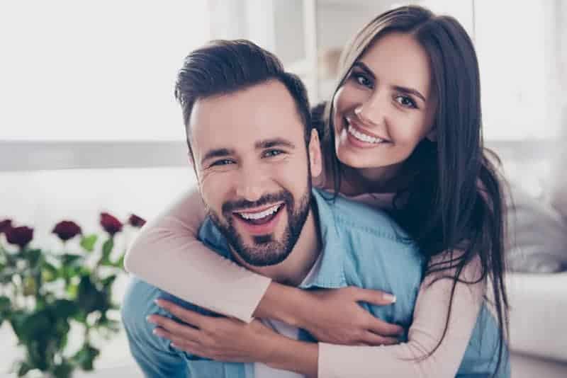 Frau, die einen lächelnden Mann umarmt