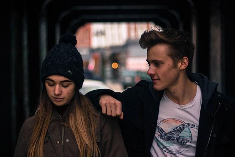 Frau ignoriert Mann, der sich auf ihre Schulter stützt und mit ihr flirtet
