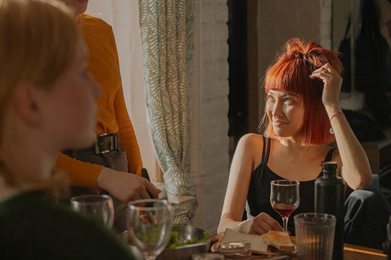Frau mit roten Haaren schaut ihre Freunde an, während sie ein Glas Wein hält