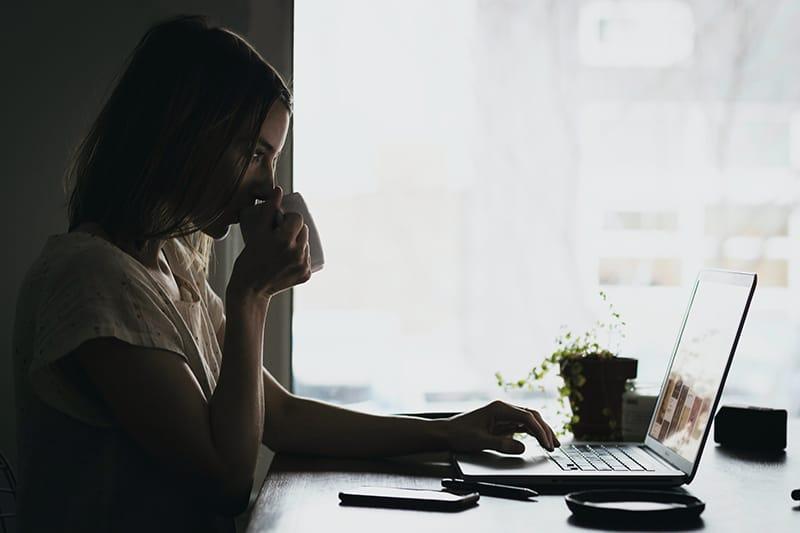 Frau trinkt Kaffee während der Arbeit am Laptop