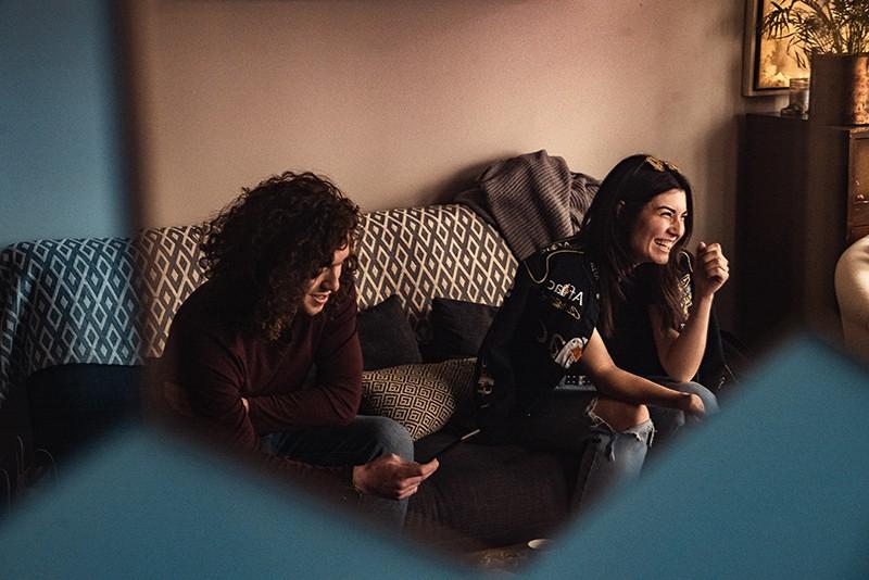 Freunde lachen und reden, während sie auf der Couch sitzen