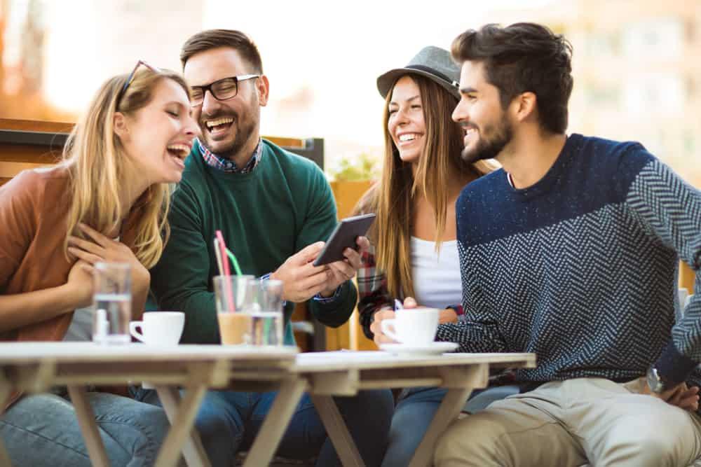Freunde sitzen am Tisch und lachen