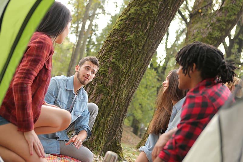 Freunde sitzen auf der Decke im Wald und reden