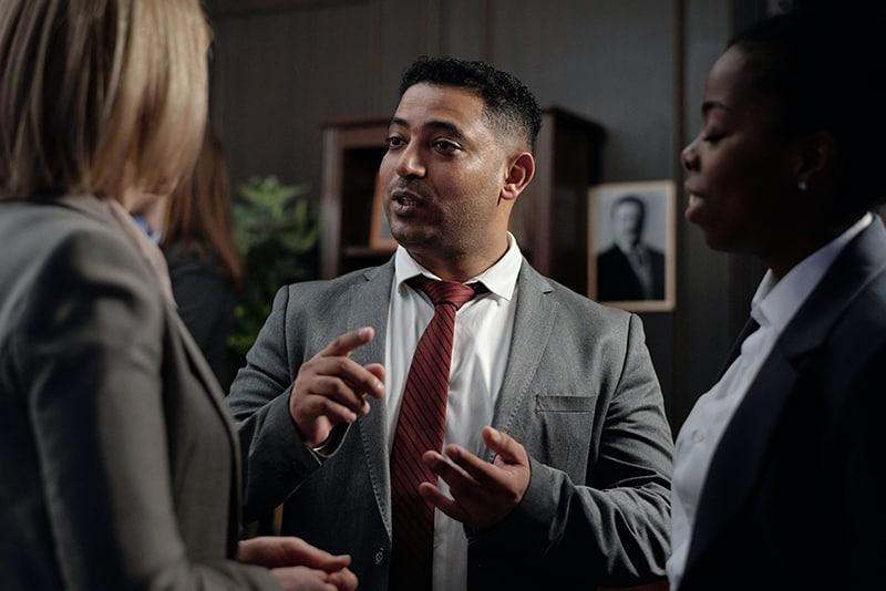 Geschäftsmann im Gespräch mit seinen Kolleginnen im Stehen
