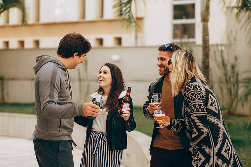 Gruppe lachender Freunde, die ihre Getränke halten, während sie im Hinterhof stehen