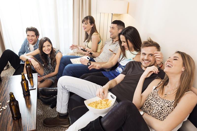 Gruppe lachender Freunde, die im Wohnzimmer sitzen und rumhängen