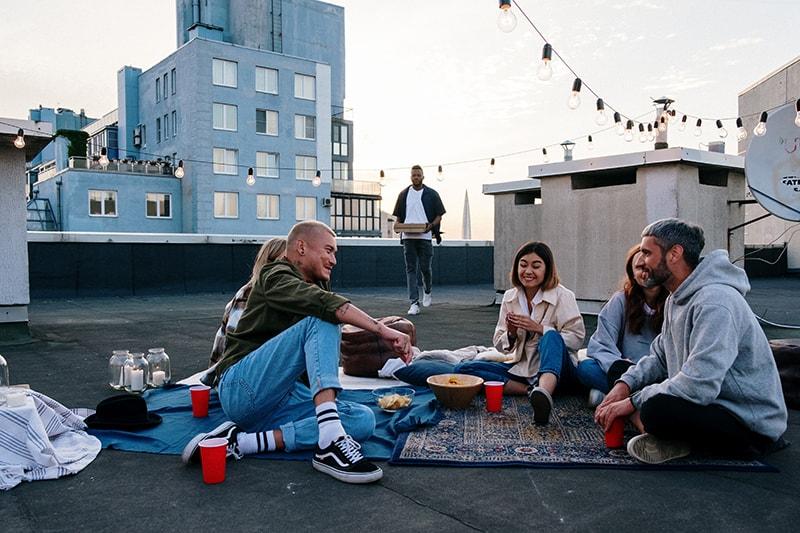 Gruppe von Freunden, die auf dem Dach sitzen und Wahrheit oder Pflicht spielen