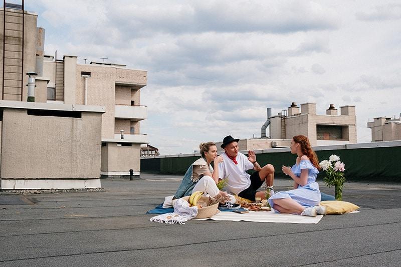 Gruppe von Freunden, die auf dem Dach sprechen, während sie auf dem Boden sitzen