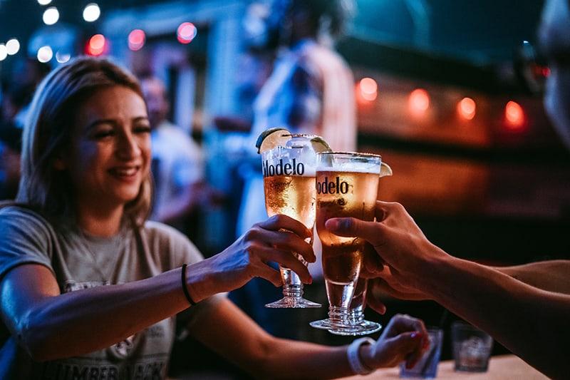 Gruppe von Freunden, die an der Bar mit einem Bier anstoßen