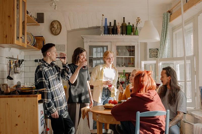 Gruppe von Freunden, die zusammen Wein in der Küche trinken