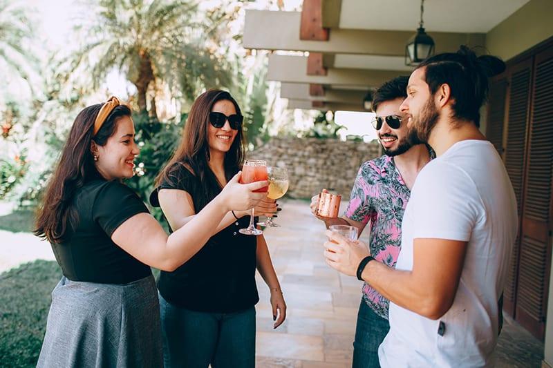 Gruppe von Freunden hält Getränke und macht einen Toast