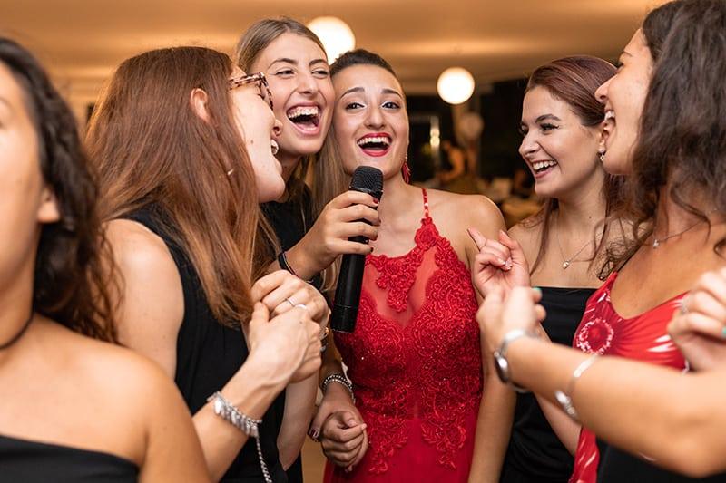 Gruppe von Freundinnen lacht, während einer von ihnen Mikrofon hält