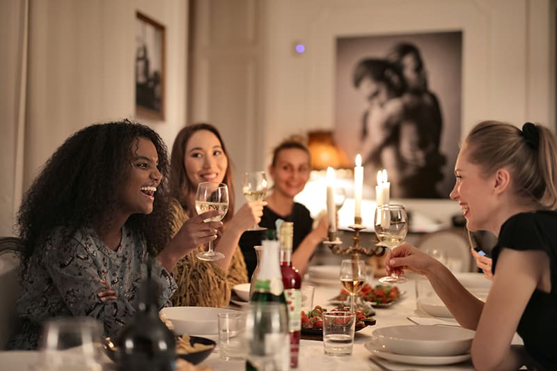Gruppe von Freundinnen, die lachen, während sie Wein während eines Abendessens trinken